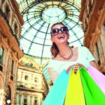 Happy woman with shopping bags in Galleria Vittorio Emanuele